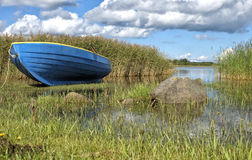 Blue boat on the shore of the lake in the tall grass Royalty Free Stock Images