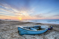 Blue Boat at Sunrise. Turquoise blue fishing boat at sunrise on Bournemouth beach with pier in far distance Royalty Free Stock Images