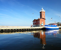Blue boat tied to wharf. A view of a small, blue and white boat tied to a wharf with a red brick building Royalty Free Stock Photos