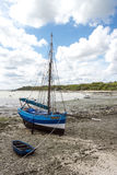 Blue boat at time of low tide, northern coast Stock Photo