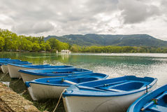Blue boats lake Banyoles view. The lake of Banyoles in Catalonia with some leisure boats tied up and a Pesquera fishing building in the background stock images