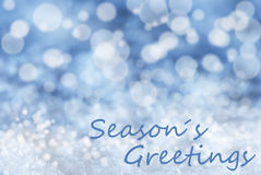 Blue Bokeh Christmas Background, Snow, Text Seasons Greetings Royalty Free Stock Images