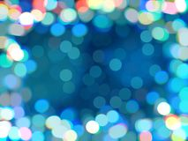 Blue bokeh defocused background. Frame of luminous shiny colored confetti, blurred backdrop