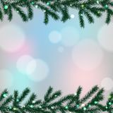 Blue bokeh light effect with fir tree branches frame. Christmas background Royalty Free Stock Photos