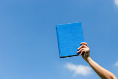 Blue book in hand Royalty Free Stock Photography