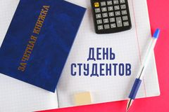 A blue book with an inscription in Russian - a student`s record book. Pen, calculator and blank notebooks on a pink background. I Stock Image