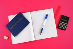 A blue book with an inscription in Russian - a student`s record book. Pen, calculator and blank notebooks on a pink background. S Stock Photos