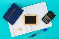 A blue book with an inscription in Russian - a student`s record book. Pen, calculator and blank notebooks on a blue background. S Royalty Free Stock Image