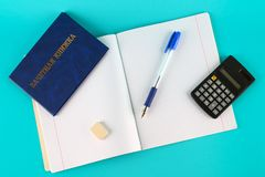 A blue book with an inscription in Russian - a student`s record book. Pen, calculator and blank notebooks on a blue background. S Stock Photography