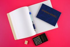 A blue book with an inscription in Russian - a student`s record book. Pen, calculator and blank notebooks on a pink background. S Stock Photo