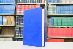 Blue book standing on table with bookshelf in background Royalty Free Stock Photography