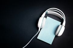 Blue book with a white headphones on it on black background. Au stock photography
