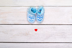 Blue booties for the boy and a small red heart on a white wooden royalty free stock images