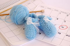 Blue booties and Calendar. Blue baby booties, yarn and knitting needles resting on calendar, date circled in red stock photography