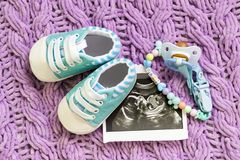 Blue booties next to baby photos with ultrasound at 20 weeks of pregnancy. The concept of awaiting boy, A son. Selective focus. Blue booties next to baby photos stock image