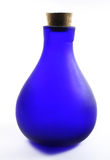 Blue Bottle. Isolated blue bottle made of frosted glass. Backlight with white background Stock Photos