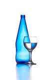 Blue bottle of glass and wineglass isolated on white.  Royalty Free Stock Images