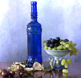 Blue bottle with grapes Stock Photography