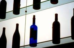 Blue bottle on a lit bar shelf. A blue bottle sitting on a backlit bar shelf among black bottles Stock Photography