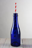 Blue Bottle with Red Striped Straw Stock Images