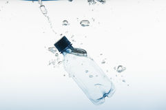 Blue Bottle Splashing into the Water Stock Images