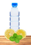 Blue bottle with water, mint and fresh yellow lemon on table iso. Lated on white background royalty free stock images