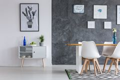 Blue bottle on white cupboard. Against wall with poster in dining room with geometric carpet Stock Image