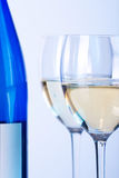Blue bottle of white wine and two wine glasses Stock Images