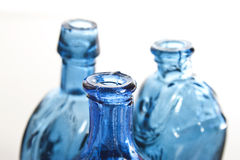 Blue bottles in close up. Three blue vintage bottles with soft focus on front bottle Royalty Free Stock Photography