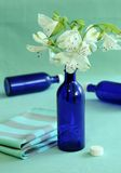 Blue bottles and flowers. Royalty Free Stock Photography