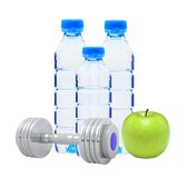 Blue bottles with water, chromed fitness dumbbells. And green apple Stock Photos