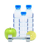Blue bottles with water, chromed fitness dumbbells, lime. And green apple isolated on white background Royalty Free Stock Photos