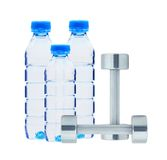 Blue bottles with water and dumbbells isolated Royalty Free Stock Photos