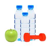 Blue bottles with water, dumbell and green apple Royalty Free Stock Image