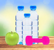 Blue bottles with water, dumbell and green apple on table over n stock photo