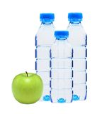 Blue bottles with water and green apple isolated Royalty Free Stock Photography