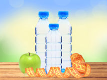 Blue bottles with water, measure tape and green apple on wooden Stock Image