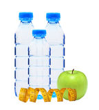 Blue bottles with water, measuring tape and green apple isolated Royalty Free Stock Photos