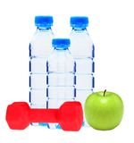 Blue bottles with water, red dumbell and green apple isolated Royalty Free Stock Photography