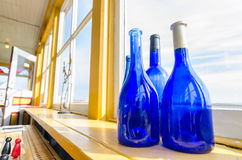 Blue bottles in a window beside the sea, Newfoundland Canada. Royalty Free Stock Images