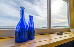 Blue bottles in a window beside the sea, Newfoundland Canada. Royalty Free Stock Image