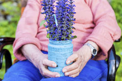 Blue bouquet of blooming flowerst in senior woman's hands Royalty Free Stock Photo