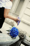 Blue bouquet and girl in blue shoes on the background. Blue bouquet and girl in blue shoes on the hands of a man in the background Stock Images