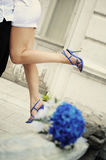 Blue bouquet and girl in blue shoes on the background. Blue bouquet and girl in blue shoes on the hands of a man in the background Stock Photography