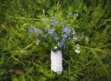 Blue bouquet lies on the green grass Stock Image