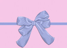 Blue Bow on Pink Background. A polka dotted blue bow over a baby pink textured background. Perfect for printing vector illustration