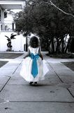Blue Bow and Small Girl. Little Girl skips through the park.  She is wearing a white long dress with a bright blue bow.  Photo is black and white Stock Image