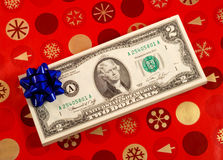 Blue bow on a stack of two dollar bills Stock Images