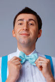 Blue Bow Tie. Cheerful young man correcting his blue bow tie Royalty Free Stock Image