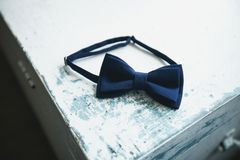Blue bow tie, a fashion accessory for a man, groom or businessman, on an old shabby, peeling wooden table, close-up. Preparing the stock photography